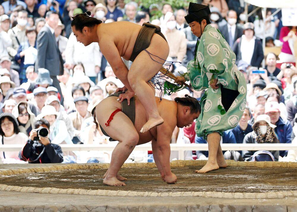 Combatentes de sumô durante combate demonstrativo em uma competição no santuário de Yasukuni, Japão.