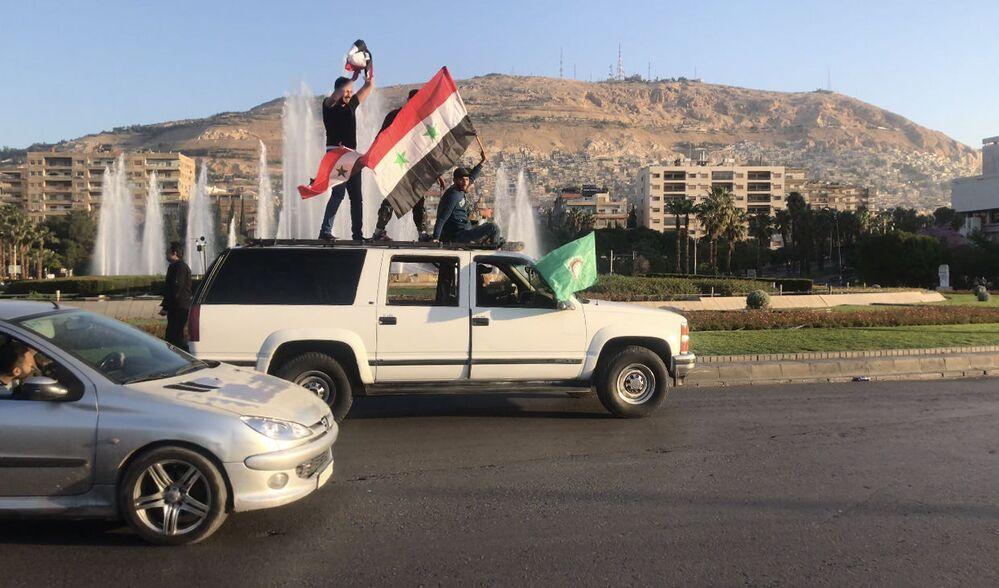 Sírios durante uma manifestação em Damasco contra os ataques aéreos da coalizão liderada pelos EUA.