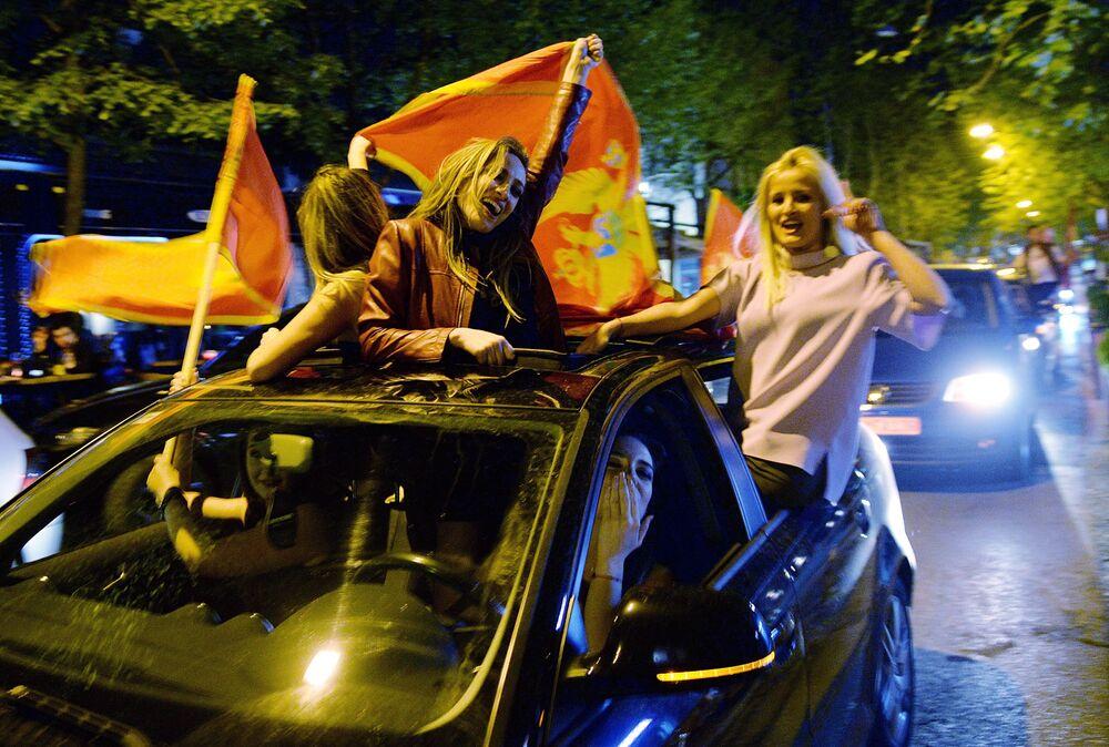 Pessoas celebrando a vitória do líder do Partido Democrático dos Socialistas de Montenegro, Milo Dukanovic, na primeira volta das presidenciais no Montenegro.