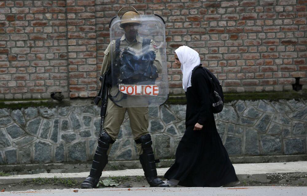 Estudante muçulmana passa perto de um policial indiano durante protesto contra estupros na cidade de Srinagar, Caxemira, Índia.