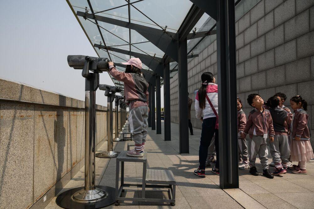 Alunos observam por binóculos a área de observação construída na zona desmilitarizada – faixa de segurança entre a Coreia do Norte e a Coreia do Sul