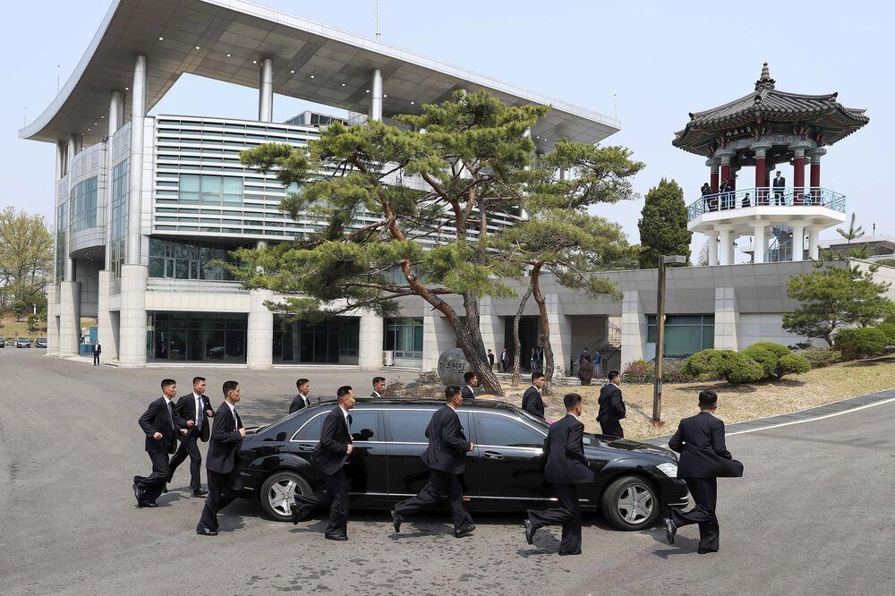 Guarda-costas escoltam o carro do líder norte-coreano, Kim Jong-un, no trajeto de volta à Coreia do Norte durante a pausa para almoço