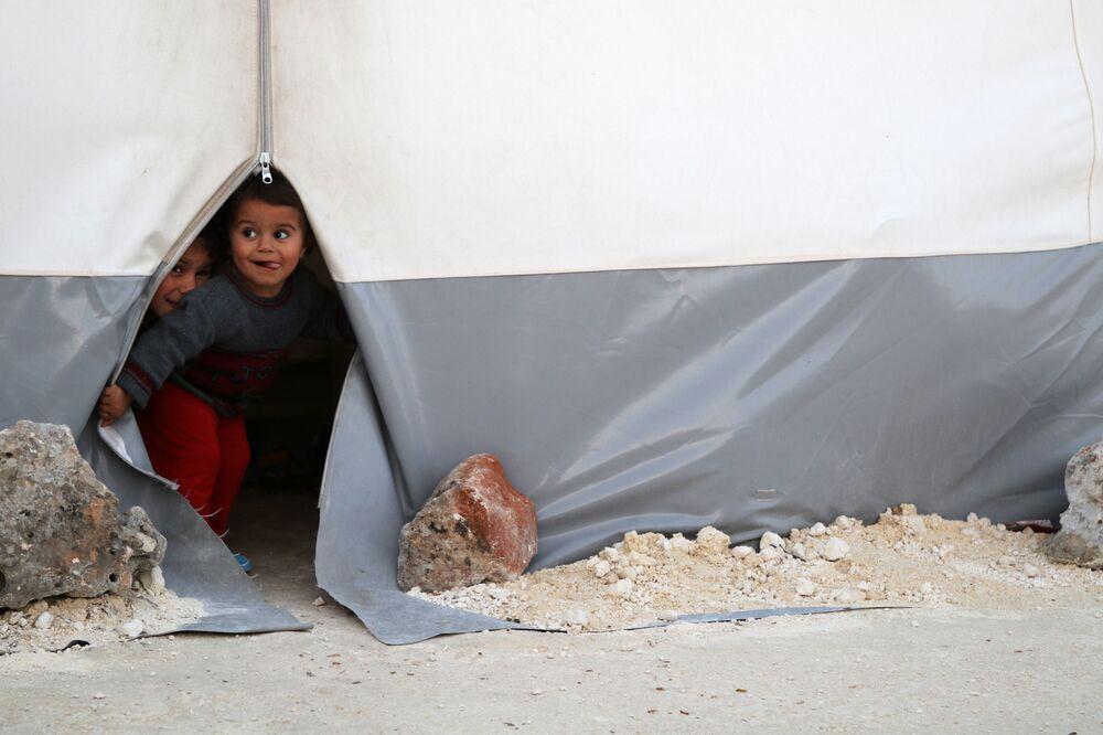 Crianças espreitam de uma tenda no campo de refugiados temporário para deslocados de Ghouta Oriental na província de Idlib