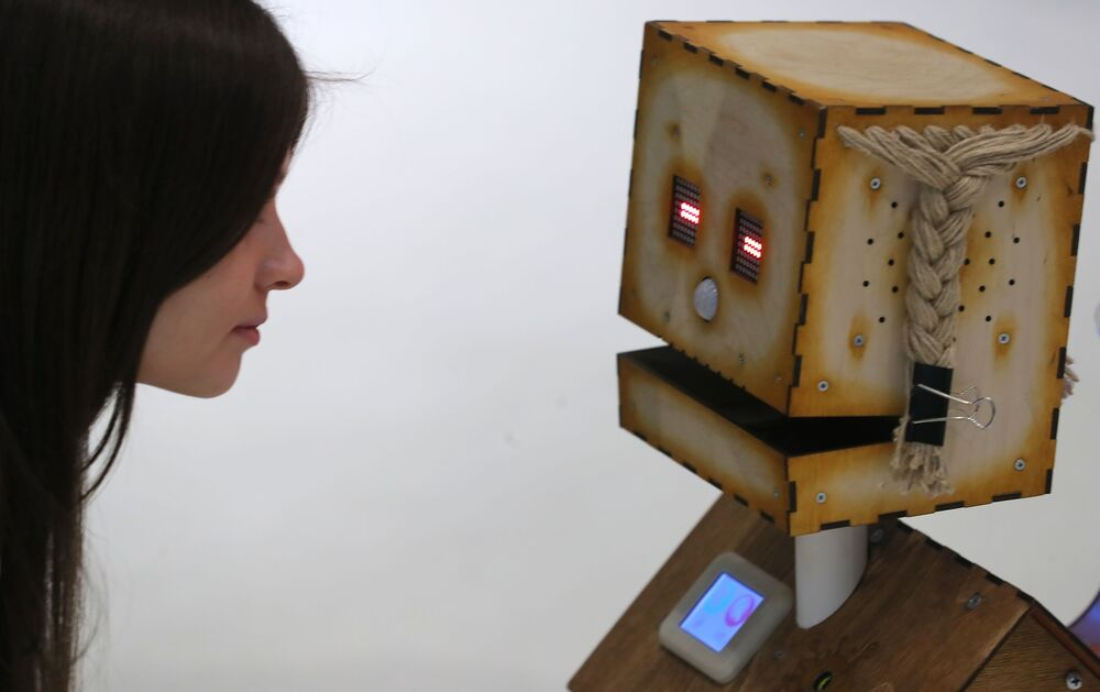 Visitante da exposição de robótica no centro de inovações de Skolkovo olha para o robô Derevyaka, em Moscou