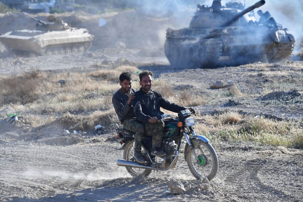 Soldados de moto perto do campo de refugiados Yarmouk, no sul de Damasco