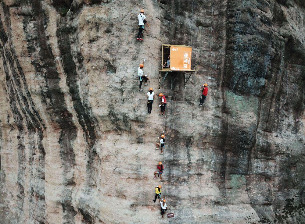 Pessoas praticam escalada na cidade de Pingjiang, na China