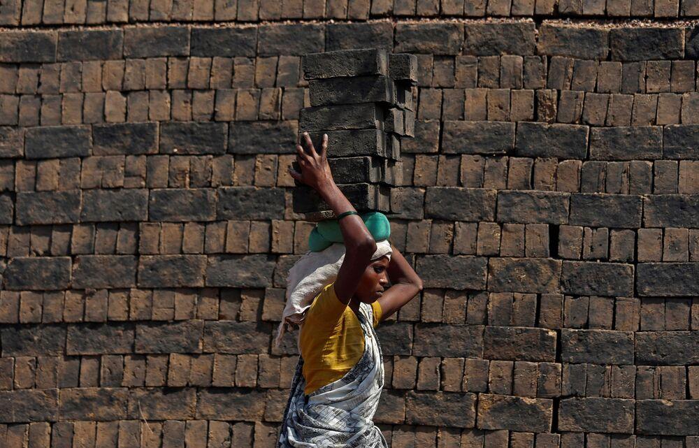 Mulher carrega tijolos sobre sua cabeça na cidade de Mumbai, na Índia