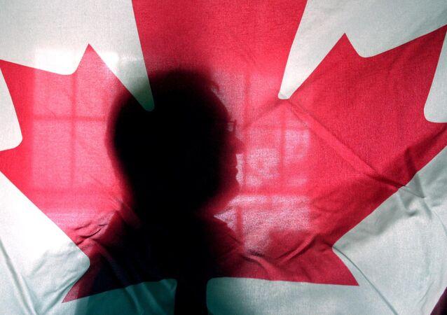 Silhueta atrás de uma bandeira do Canadá na Universidade de Vermont em Burlington, Virgínia (foto de arquivo).