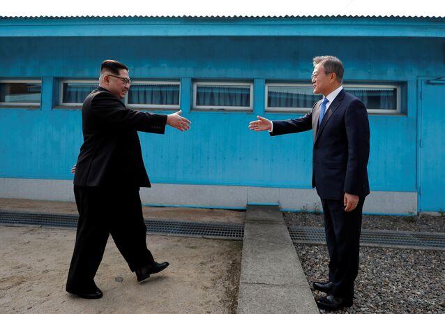 Líderes da Coreia do Norte, Kim Jong-un, e da Coreia do Sul, Moon Jae-in, apertam as mãos durante encontro na localidade de Panmunjom, na zona desmilitarizada que separa os dois países, 27 de abril de 2018