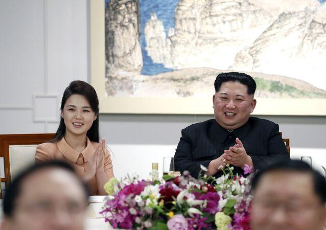 O líder da Coreia do Norte, Kim Jong-un, com sua esposa Ri Sol-jul durante encontro com o presidente sul-coreano, Moon Jae-in, e sua esposa na zona desmilitarizada entre as duas Coreias, 27 de abril de 2018