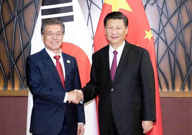 Moon Jae-in (à esquerda), presidente da Coreia do Sul aperta a mão de Xi Jinping (à direita), presidente da China durante encontro do Fórum de Cooperação Econômica Ásia-Pacífico (APEC).