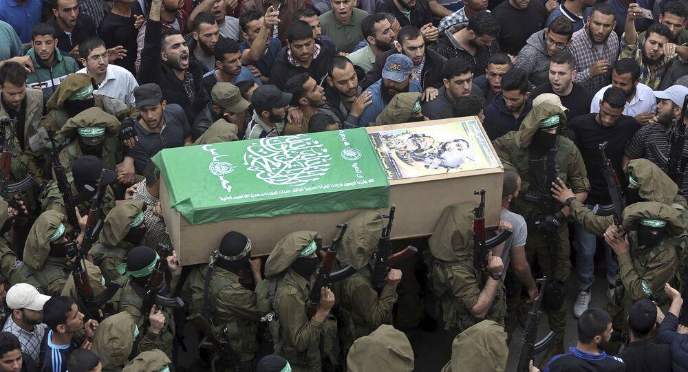Homens armados do Hamas carregam caixão de um de seus homens na Faixa de Gaza neste domingo (6).