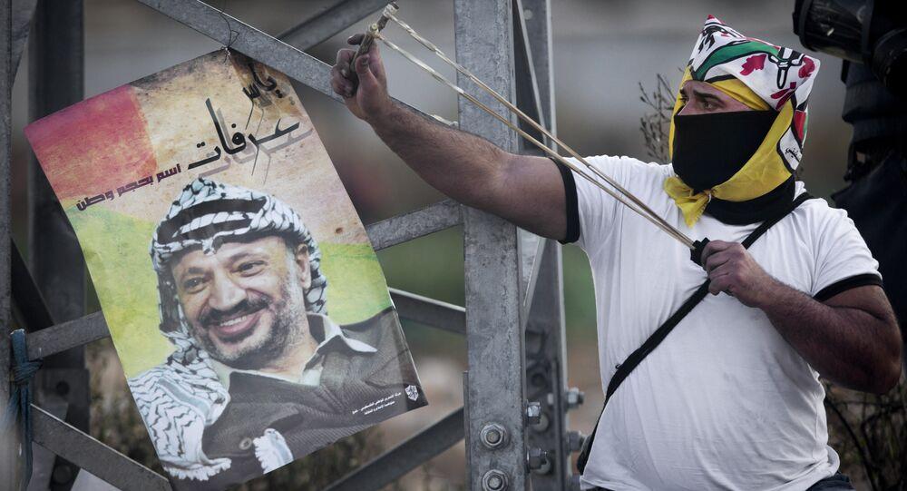Manifestante palestino usa estilingue para atirar pedras contra forças de segurança israelenses durante confrontos após um protesto para marcar o 11º aniversário da morte do líder palestino Yasser Arafat, na cidade de Ramallah, Cisjordânia, 11 de novembro de 2015.