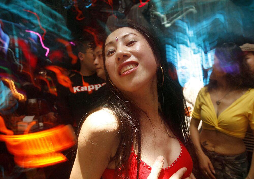 Professora de dança do ventre, Yi Hong, e seus alunos, descansam em um bar após as aulas, na China