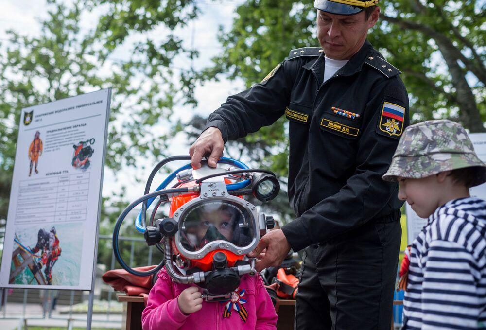 Menina testando um equipamento especial na exposição em Sevastopol