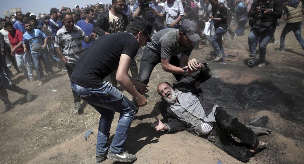 Palestino é socorrido após ser baleado em protesto na Faixa de Gaza. Foto de 14 de maio de 2018.