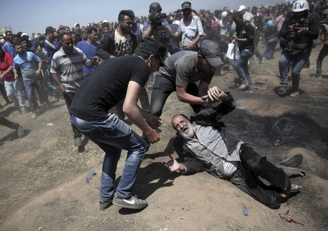 Um idoso palestino cai no chão depois de ser baleado por tropas israelenses durante um protesto na fronteira da Faixa de Gaza com Israel, a leste de Khan Younis.