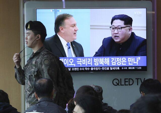 Soldado sul-coreano passando por uma TV que está mostrando fotos do Secretário de Estado dos EUA, Mike Pompeo, e do líder norte-coreano, Kim Jong-un