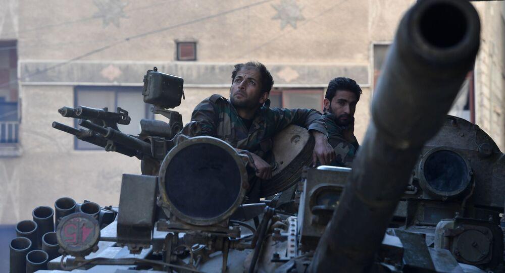 Tripulação de tanque do exército sírio na área do antigo campo de refugiados palestinos Yarmouk, no subúrbio a sul de Damasco