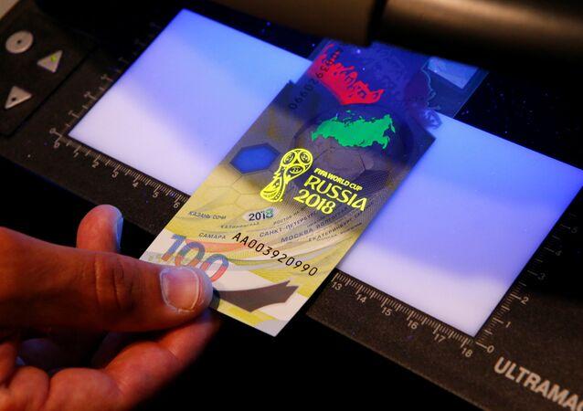 Diretor geral da estatal Arkady Trachuk mostra a marca d'água da cédula de 100 rublos emitida especialmente para a Copa do Mundo de 2018 pelo banco central da Rússia.