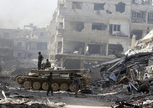 Forças governamentais sírias em rua destruída nos arredores de Damasco