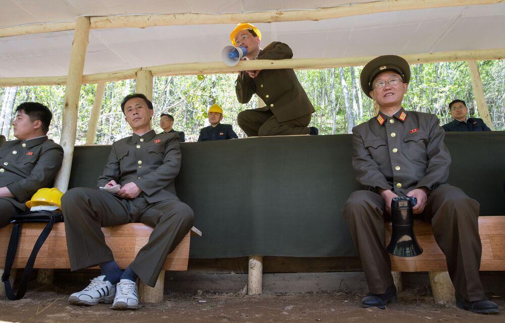 Oficiais durante a explosão das minas, que eram usadas para testes de bombas nucleares, do polígono nuclear de Punggye-ri, no norte da Coreia do Norte