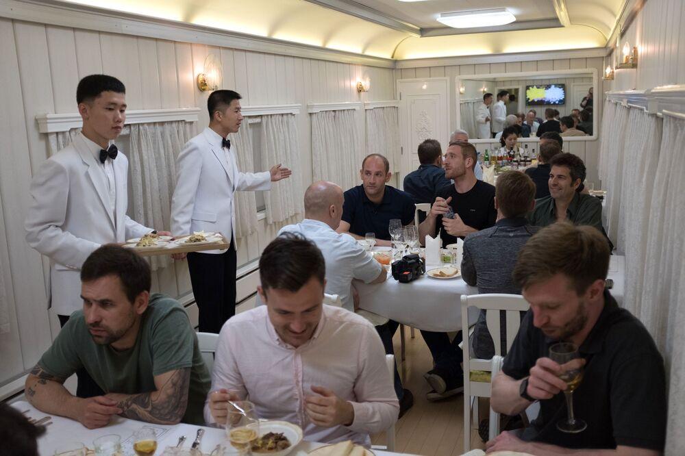 Jornalistas no vagão do restaurante do trem, no qual foram assistir ao fechamento do polígono de Punggye-ri, Coreia do Norte
