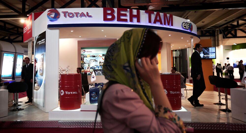 Empresária sul-coreana falando ao telefone em frente à tenda da empresa francesa de óleo e gás Total, durante uma feira internacional de negócios no Irã (foto de arquivo)