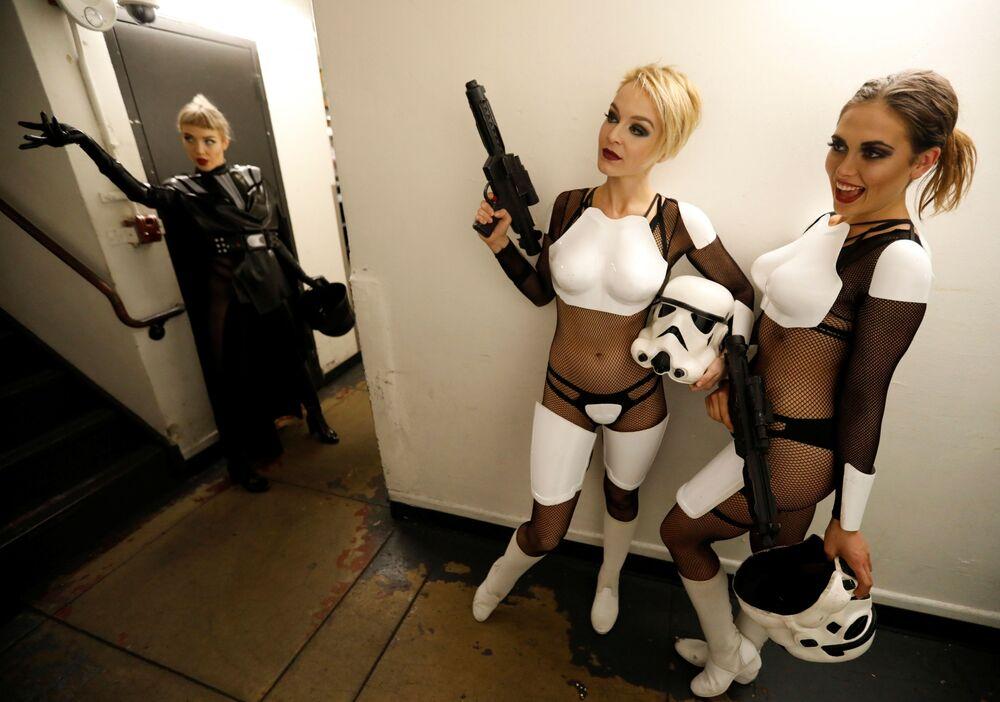 Dançarinas em trajes temáticos posam para fotógrafo nos bastidores do show de paródia dedicado ao filme Guerra nas Estrelas