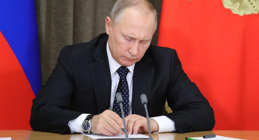 Vladimir Putin assinando um documento durante a reunião dedicada ao reequipamento das Forças Armadas da Rússia, novembro de 2017 (foto de arquivo)