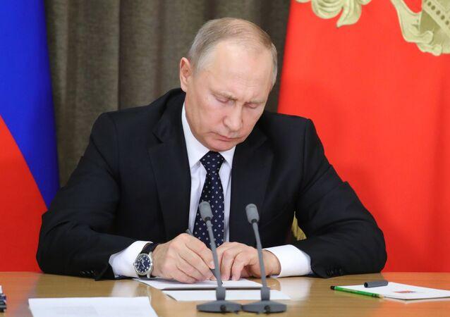 Vladimir Putin assinando um documento durante a reunião dedicada ao reequipamento das Forças Armadas da Rússia, novembro de 2017