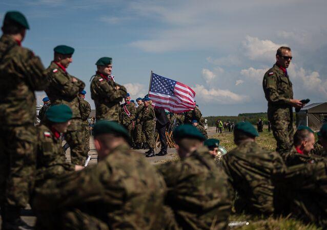 Soldados aguardam cerimônia de abertura da seção norte do escudo antimíssil em base militar na Polônia com bandeira dos EUA no plano de fundo