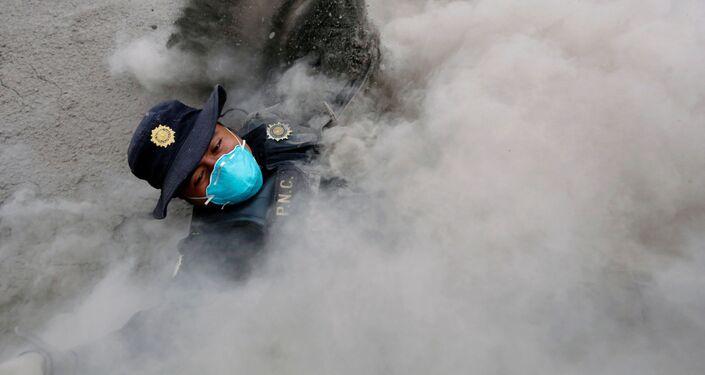 Policial tropeça enquanto foge das novas emissões de cinzas do vulcão Fogo, Guatemala, em 4 de junho de 2018