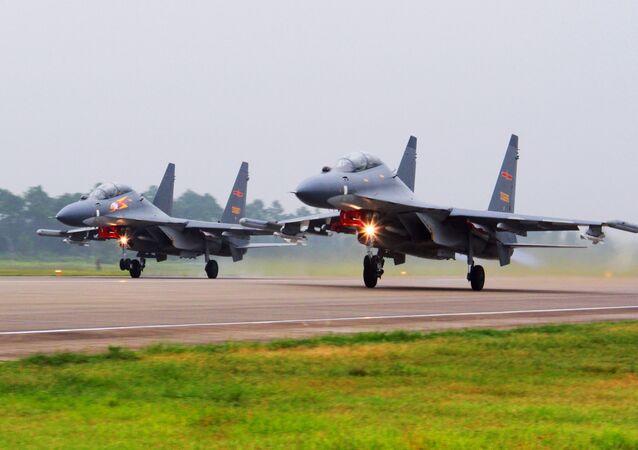 Nesta foto de arquivo, dois aviões de combate SU-30 chineses decolam de um local não-especificado para patrulhar o Mar do Sul da China.