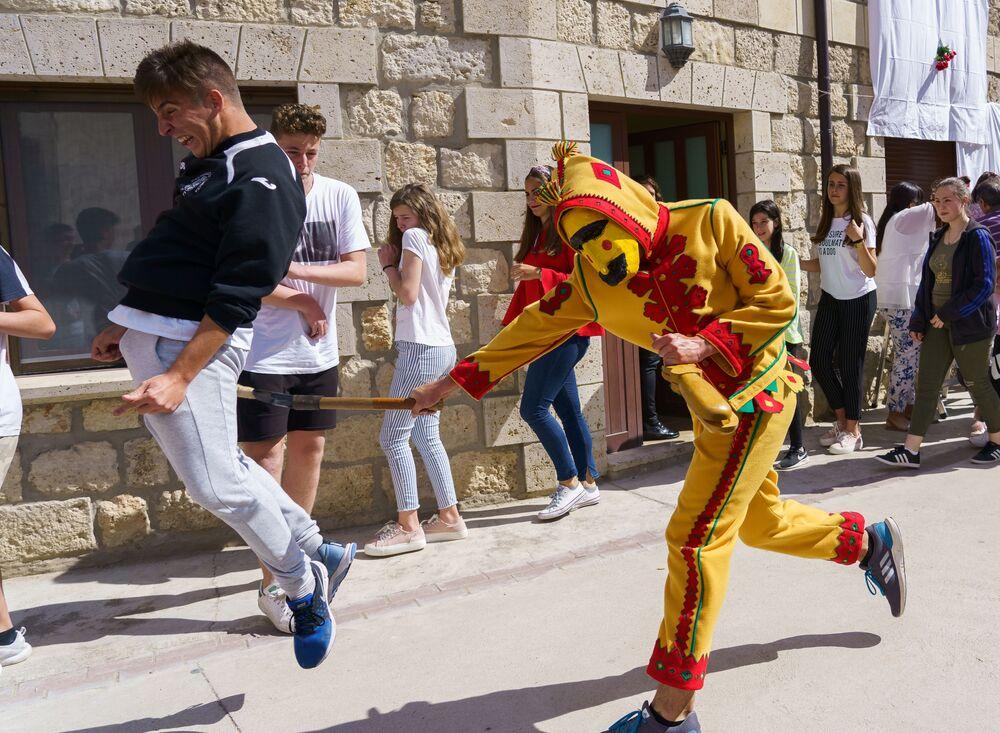 Um colacho (pessoa vestida de diabo) perseguindo pessoas durante o festival de saltos El Salto del Colacho, na povoação de Castrillo de Murcia, Espanha