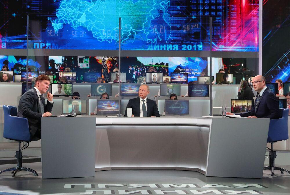 O presidente russo Vladimir Putin respondendo às perguntas da população durante a Linha Direta anual