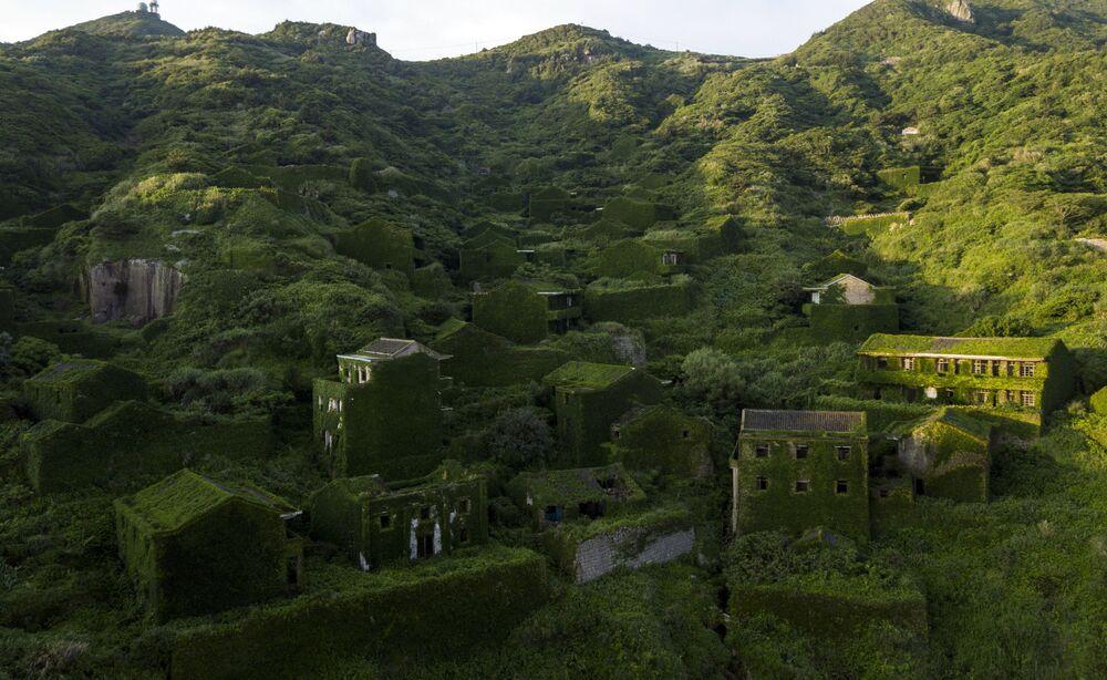 Casas cobertas por vegetação na povoação abandonada de Houtouwan, China.