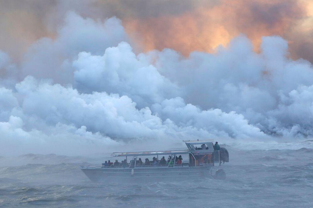 Pessoas olhando desde um barco a lava correndo ao oceano Pacífico durante as erupções do vulcão Kilauea, no Havaí.