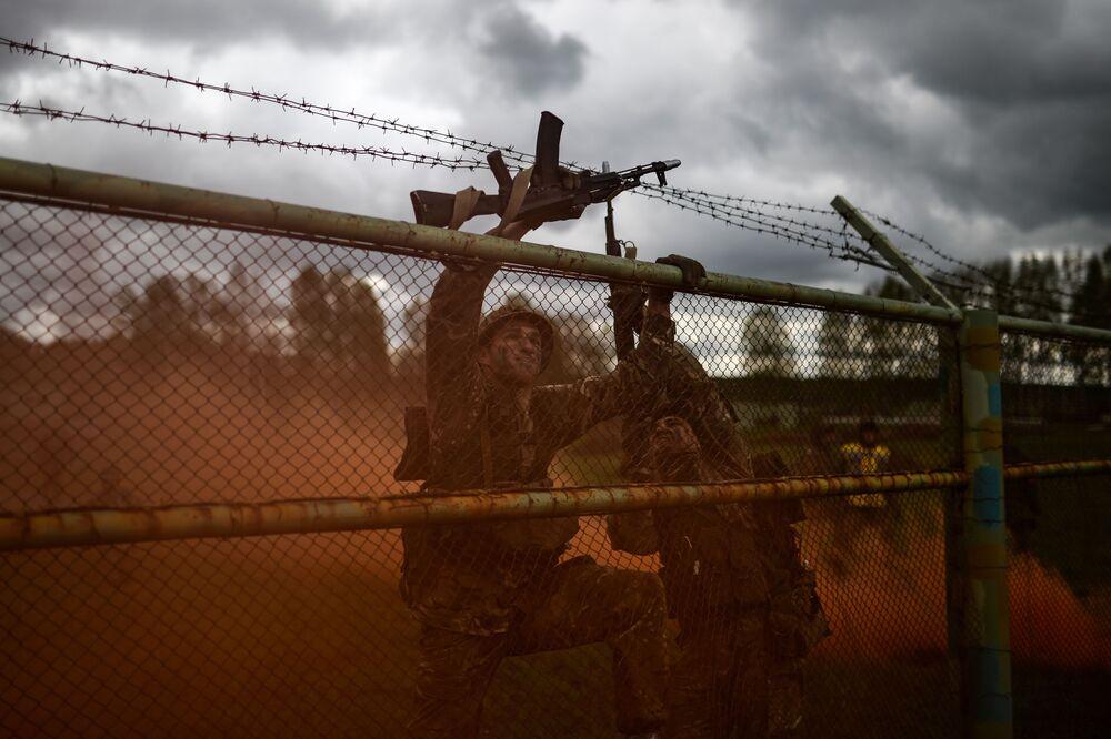 Participantes de um concurso militar na região de Novossibirsk superando obstáculos.