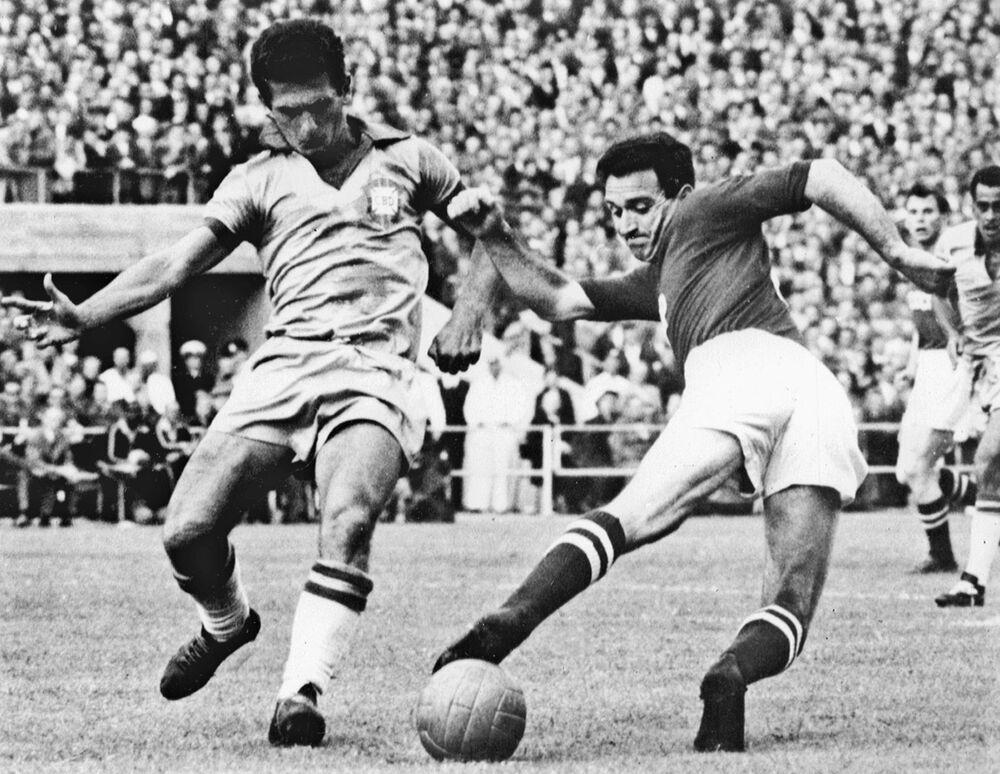 O atacante Nikita Simonyan da União Soviética perde o controle da bola sob pressão do meia brasileiro Orlando durante a partida da primeira rodada da Copa do Mundo entre o Brasil e a União Soviética, no dia 15 de junho de 1958. O Brasil venceu a URSS por 2 a 0 com dois gols do atacante Vavá.