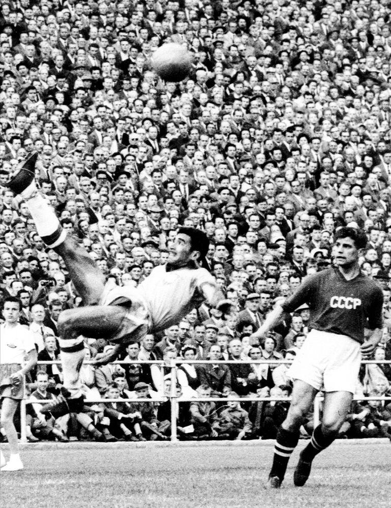 O zagueiro brasileiro Nilton Santos chuta a bola para longe ao perceber aproximação do atacante soviético Alexander Ivanov durante a partida da primeira fase da Copa do Mundo em 1958. O Brasil venceu por 2x0.