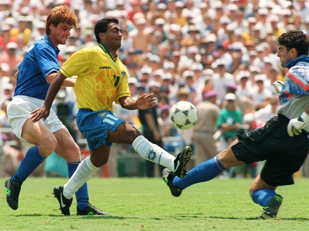 O atacante brasileiro Romário passa pelo zagueiro italiano Luigi Apolloni enquanto tenta chutar a bola sobre o goleiro Gianluca Pagliuca, em 17 de julho de 1994, durante a final da Copa do Mundo.