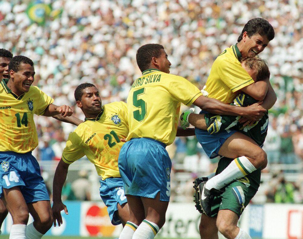 O atacante brasileiro Bebeto pula para abraçar o goleiro Claudio Taffarel, enquanto companheiros de equipe Cafu, Viola e Mauro Silva comemoram após o italiano Roberto Baggio perder sua cobrança de pênalti no final da disputa da Copa do Mundo em 17 de julho de 1994.