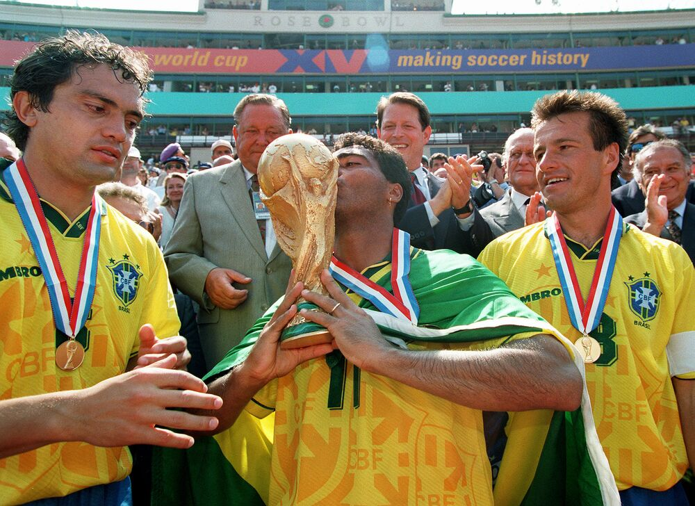 O atacante brasileiro Romário beija o troféu da Copa do Mundo da FIFA, com seus companheiros de equipe Branco e Dunga, depois que o Brasil derrotou a Itália por 3 x 2 nos pênaltis.
