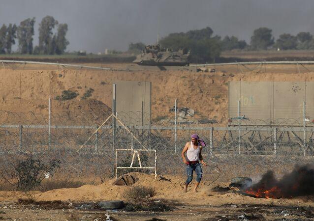 Manifestante palestino ao lado da cerca israelense durante um protesto na fronteira entre Israel e Gaza, no sul da Faixa de Gaza, em 5 de junho de 2018