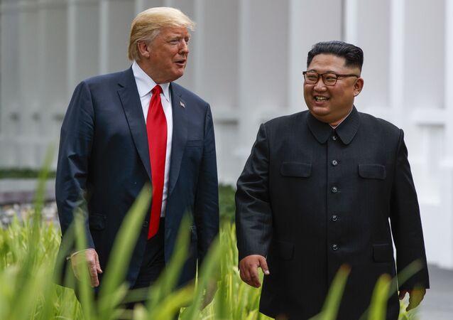 Presidente dos EUA, Donald Trump, e o líder norte-coreano, Kim Jong-un, passeiam após um almoço de negócios no âmbito da cimeira em 12 de junho de 2018, em Singapura
