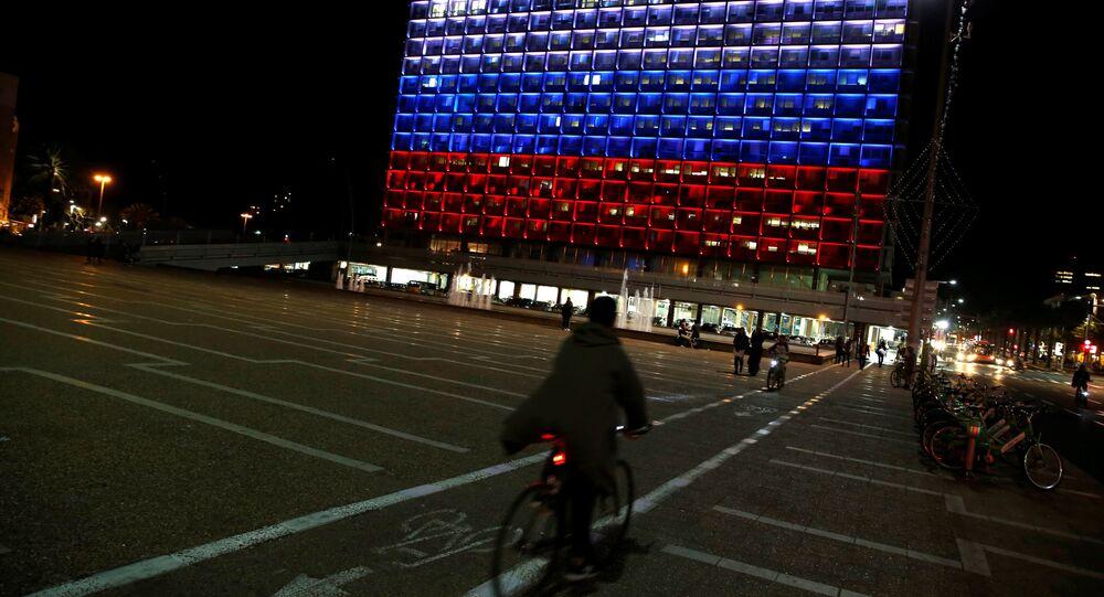 Ciclista pedala em Tel Aviv em frente a um prédio iluminado com as cores da bandeira russa