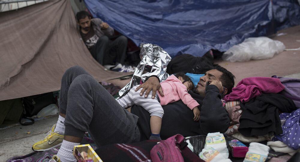 Um pai e uma criança migrantes aguardam fora de um prédio para pedir asilo nos EUA em Tijuana, México.