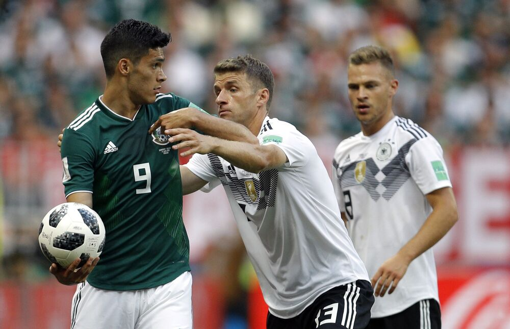 O jogador alemão Thomas Mueller tenta tomar a bola do mexicano Raul Jimenez durante jogo entre as seleções no 1º jogo do grupo F da Copa do Mundo de 2018.