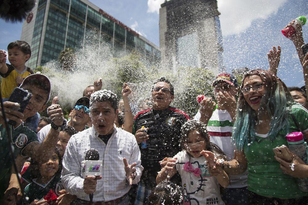 Um repórter e torcedores cobertos com espuma durante a celebração da vitória do México sobre a Alemanha durante a Copa do Mundo, a festa acontece em frente ao monumento Anjo da Independência, na cidade do México.